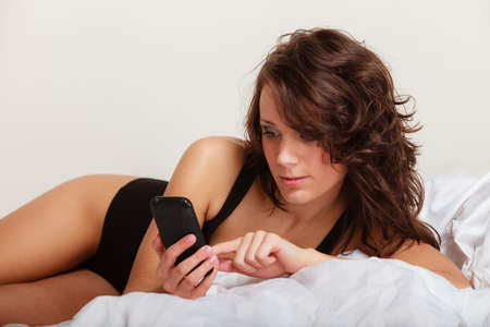 sms message: Sexy lazy girl in body underwear lying on bed texting on mobile phone. Woman relaxing lazing in bedroom at the morning.
