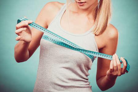 Fitness donna ragazza adatta in abiti sportivi con nastro di misura che misura il suo seno dimensioni petto su blu