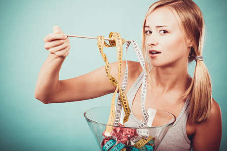 Diet, healthy food, weight loss and slim body concept. Fit fitness girl holding bowl eating colorful measuring tapes Banque d'images