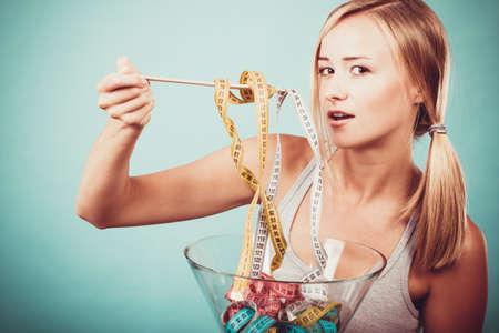 comiendo: Dieta, alimentos saludables, la p�rdida de peso y el concepto de cuerpo delgado. Muchacha de la aptitud Fit taz�n celebraci�n de comer cintas de medici�n de colores Foto de archivo