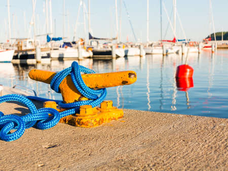 mooring bollard: Yellow mooring bollard with blue rope in marina yachts in the background Stock Photo