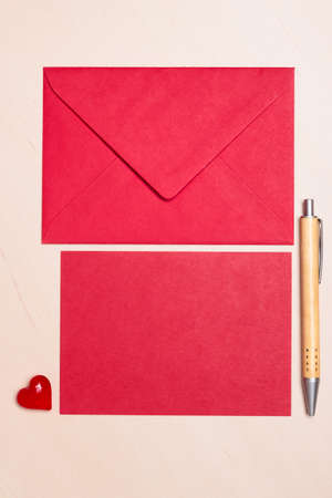 envelope: Red blank sheet of paper with envelope and little heart, pen on wooden surface. Background for valentines day or wedding card.