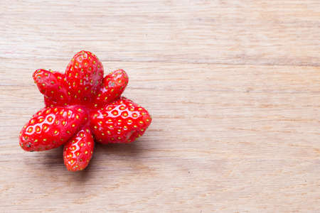 odd: Healthy nutrition diet food modification. Red odd single strawberry fruit on wooden table board copy space text area