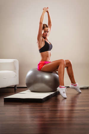 sports training: Sport, training, gym and lifestyle concept. Young attractive slim woman in sportwear doing fitness exercises with fit ball at home