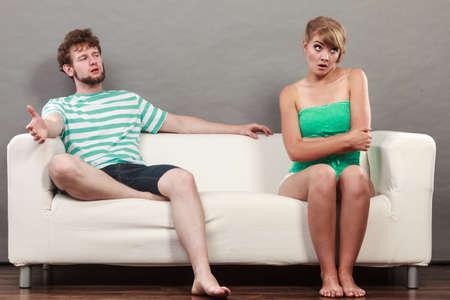 pareja discutiendo: Mala relaci�n de conceptos. Hombre y mujer en desacuerdo. Pareja joven sentado en el sof� en casa con la disputa, la esposa y el marido ofendido infeliz
