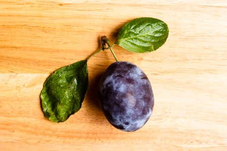 ciruela pasa: Single prune plum fruit with green leaves on wooden table Foto de archivo