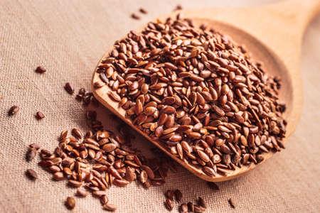 semilla: Alimentos saludables para prevenir enfermedades del corazón y el sobrepeso. Las semillas de lino de linaza en la cuchara de madera sobre fondo de arpillera