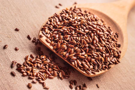 heart healthy: Healthy food for preventing heart diseases and overweight. Flax seeds linseed on wooden spoon burlap background