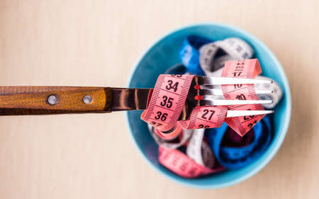 losing control: Diet food healthy lifestyle and slim body concept. Many colorful measuring tapes in blue bowl on table with fork, top view Stock Photo