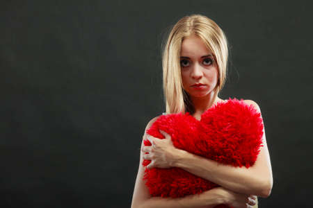 heartbreak issues: Broken heart love concept. Sad unhappy woman hugging red heart pillow dark background