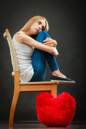 heartbreak issues: Broken heart love concept. Sad unhappy woman sitting on chair red heart pillow on floor dark background Stock Photo
