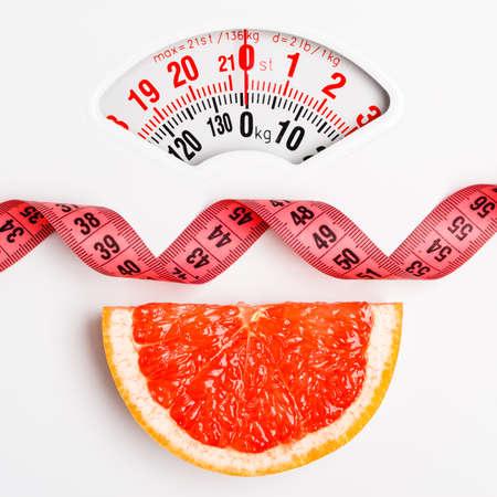 Concepto de dieta baja delgada comer sano. Rodaja de pomelo primer con cinta de medición en la escala de peso blanco Foto de archivo
