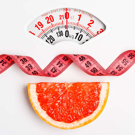 weight control: Dieting healthy eating slim down concept. Closeup grapefruit slice with measuring tape on white weight scale Stock Photo
