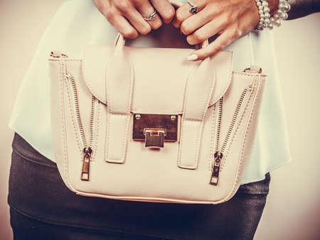 Elegant outfit. Female fashion. Girl in fashionable clothes holding bag handbag.