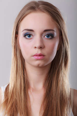 rubia ojos azules: Primer retrato atractiva mujer pensativa, ojos azules rubia chica pelo largo en gris Foto de archivo