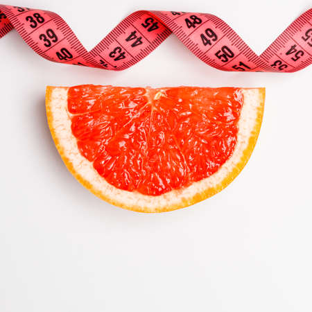 eating area: Diet healthy eating and slim body concept. Closeup red measuring tape centimeter and grapefruit copy space text area