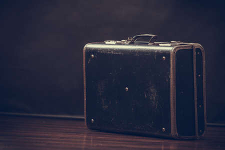 antique suitcase: Old retro style scratched suitcase on dark background