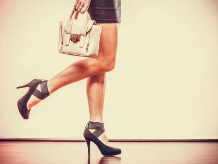 mode: Elegante outfit. Vrouwelijke mode. Meisje in modieuze hoge hakken schoenen rok bedrijf handtas.