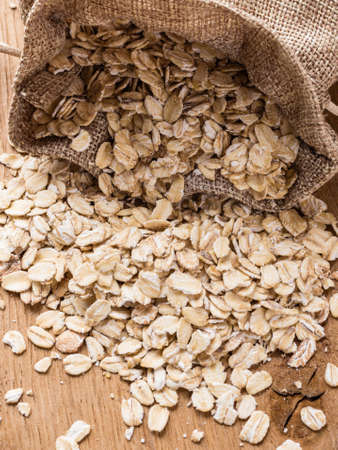 lowering: Dieting. Oat cereal in burlap sack on wooden surface. Healthy food for lowering cholesterol, protect heart. Stock Photo