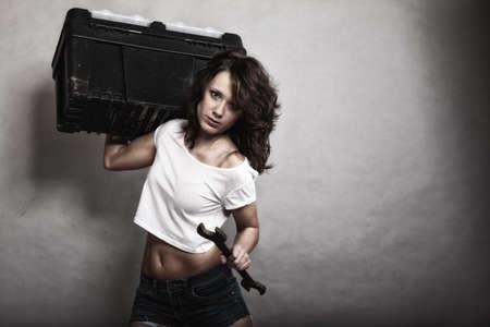 sexo: Igualdad entre los sexos y el feminismo. Muchacha atractiva que sostiene la caja de herramientas y llave herramienta llave. Mujer atractiva que trabaja como reparador o mecánico Foto de archivo