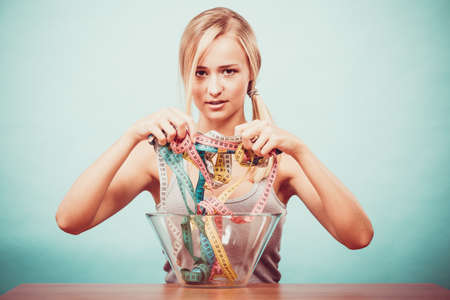 fatness: Diet, healthy food, weight loss and slim body concept. Fit fitness girl holding bowl eating colorful measuring tapes Stock Photo