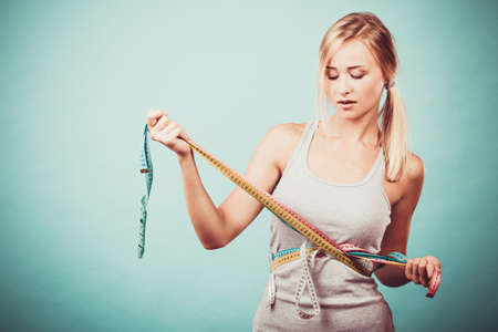 waistline: Weight loss, slim body, healthy lifestyle concept. Fit fitness girl measuring her waistline body with many colorful measure tapes on blue