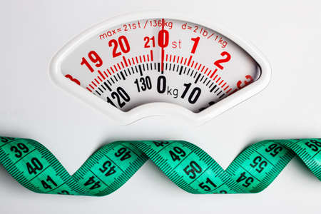 Dieting weightloss slim down concept. Closeup measuring tape on white weight scale Stockfoto