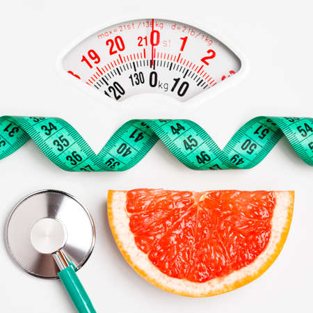 Diet healthy eating weight control concept. Grapefruit with measuring tape and stethoscope on white scales