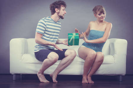 refusing: Couple sitting on couch at home. Young man giving offended woman gift box, girl refusing to accept present Stock Photo