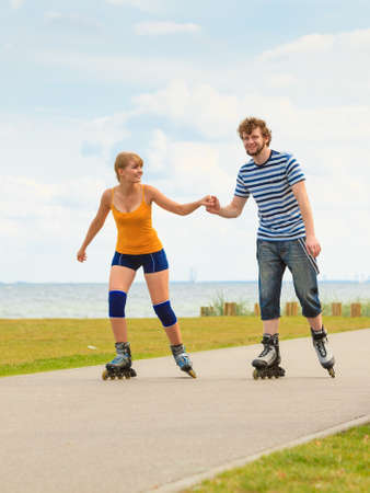 inline skater: Holidays, active people and friendship concept. Young fit couple on roller skates riding outdoors on sea shore, woman and man rollerblading together on the promenade Stock Photo