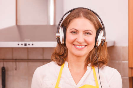 making music: Cooking and preparing food concept. Happy relaxed beauty woman housewife chef with earphones listening music in house kitchen making dinner meal.