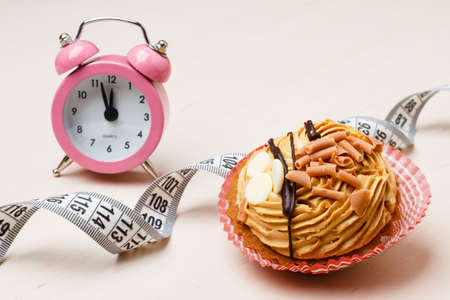 gluttony: Gluttony and not eat junk sugar foods concept. Time for slimming. Cake cupcake measuring tape and alarm clock on kitchen table