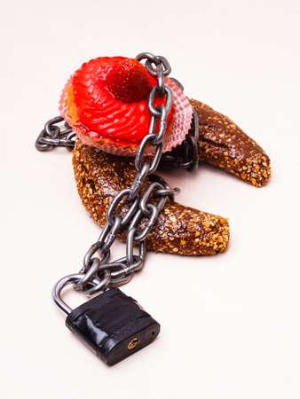 azucar: Az�car Dieta concepto adicci�n a la comida dulce. Magdalena de la torta envuelta en cadena de metal y candado