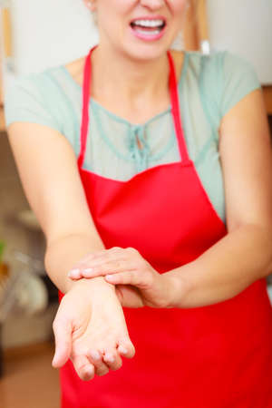 Mature woman checking pulse on wrist. Stressed female in kitchen.