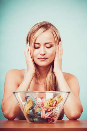 food woman: Diet, healthy eating, weight loss and slim body concept. Fit fitness girl and bowl with many colorful measuring tapes, young woman bored of dieting