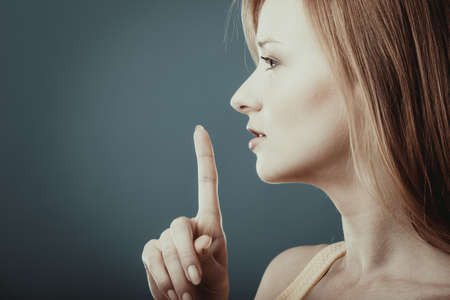 secrecy: Closeup woman asking for silence or secrecy with finger on lips hush hand gesture, on blue background