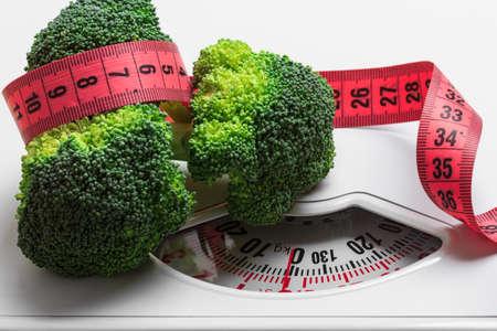 Hacer dieta alimentación saludable delgado concepto de control de peso. Brócoli verde del primer con la cinta de medición en escamas blancas
