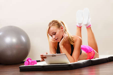 healthy sport: Fitness woman blonde fit girl lying on floor and looking into tablet pc