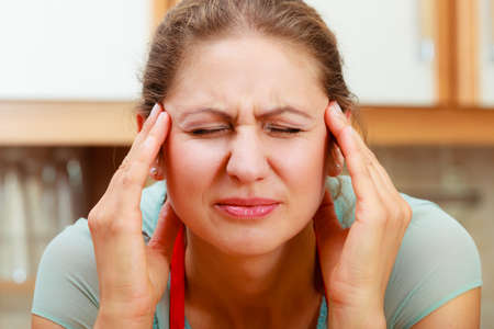 Mature woman suffering from headache migraine pain. Stressed female in kitchen. Standard-Bild