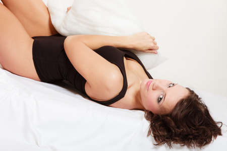 awaking: Sexy lazy girl in black body lying with pillow on the bed. Young attractive woman relaxing lazing in bedroom at morning. Stock Photo
