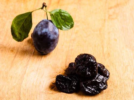 ciruela pasa: La comida sana, buena cocina. Primer ciruelas secas y frutos de ciruela fresca en la mesa de madera rústica