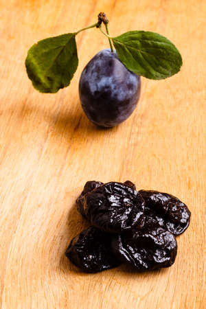prune: Healthy food, good cuisine. Closeup dried plums and fresh prune fruit on wooden rustic table