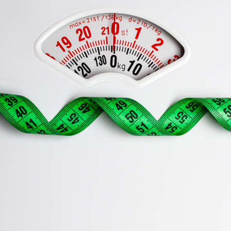 weightloss: Dieting weightloss slim down concept. Closeup measuring tape on white weight scale copy space text area Stock Photo