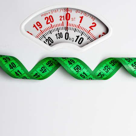 Een dieet gewichtsverlies afslanken concept. Close-up meetlint op wit gewicht schaal kopie ruimte tekstveld