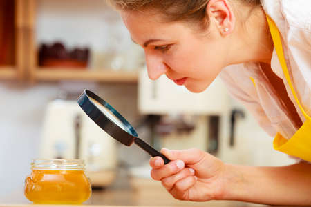 food testing: Mature woman female inspecting testing honey food with magnifying glass.