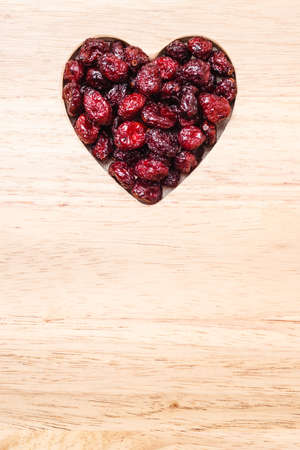 cranberry fruit: Healthy high fiber food, organic nutrition. Dried cranberries cranberry fruit in shape of heart on wooden surface background Stock Photo