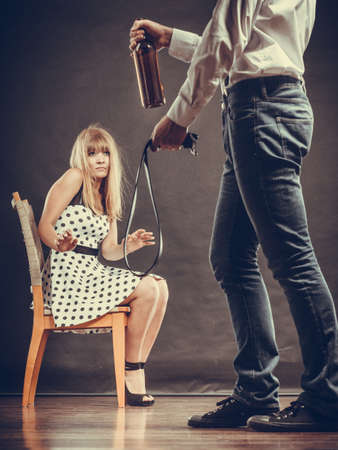 copule: Alcoholism and violence problem. Man alcoholic holding bottle beating his scared wife with belt. Woman is victim of domestic abuse. Stock Photo