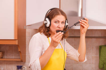 making music: Cooking and preparing food concept. Relaxed beauty woman housewife chef with earphones listening music in house kitchen making dinner meal.