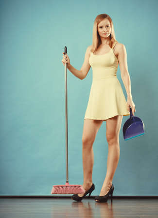 charwoman: Cleanup housework concept. Elegant sensual woman sweeping wooden floor with broom.