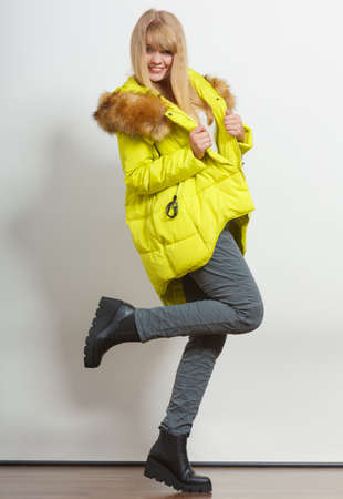 winter jacket: Beautiful smiling young fashionable girl wearing jacket with hood posing raising leg. Preparing herself clothes. Fashion in winter time. Stock Photo